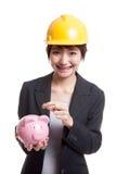 Femme asiatique d'ingénieur avec une pièce de monnaie et une banque de pièce de monnaie porcine Images stock