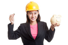 Femme asiatique d'ingénieur avec une pièce de monnaie et une banque de pièce de monnaie porcine Photographie stock libre de droits