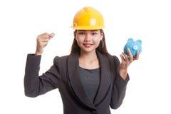 Femme asiatique d'ingénieur avec une pièce de monnaie et une banque de pièce de monnaie porcine Photo stock