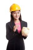 Femme asiatique d'ingénieur avec une pièce de monnaie et une banque de pièce de monnaie porcine Photographie stock