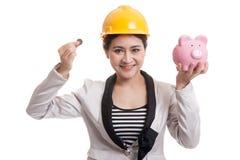 Femme asiatique d'ingénieur avec une pièce de monnaie et une banque de pièce de monnaie porcine Photo libre de droits