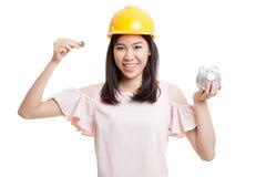 Femme asiatique d'ingénieur avec une pièce de monnaie et une banque de pièce de monnaie porcine Photos stock