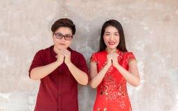 Femme asiatique dans le cheongsam traditionnel de robe chinoise et homme asiatique photographie stock