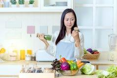 Femme asiatique dans un tablier faisant cuire la nourriture saine Photos stock