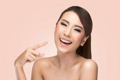 Femme asiatique de beauté de soins de la peau dirigeant son visage et rire photographie stock libre de droits