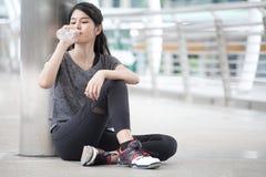 femme asiatique de forme physique faisant une pause après la séance d'entraînement exerçant le boire avec une bouteille d'eau sur image stock