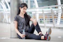 femme asiatique de forme physique faisant une pause après la séance d'entraînement s'exerçant avec une bouteille d'eau sur la rue image libre de droits