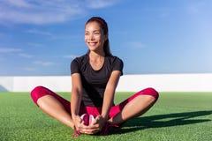 Femme asiatique de forme physique heureuse étirant des jambes en parc Image stock