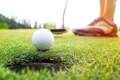 Femme asiatique de golfeur mettant la boule de golf sur le golf vert le temps réglé de soirée du soleil image libre de droits