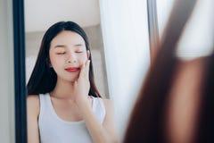 Femme asiatique de jeune beauté regardant des soins de la peau clairs de visage de contrôle de miroir photographie stock