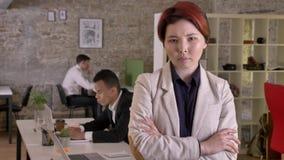 Femme asiatique de jeunes affaires avec les mains croisées regardant in camera dans le bureau moderne, sérieuses et intéressées,  banque de vidéos
