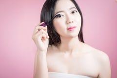 Femme asiatique de longs cheveux jeune belle appliquant le mascara d'isolement au-dessus du fond rose maquillage naturel, thérapi Photo stock