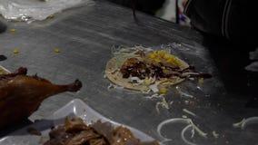 Femme asiatique de mouvement lent faisant le plat délicieux de canard avec l'enveloppe chinoise de crêpe banque de vidéos