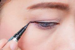 Femme asiatique de plan rapproché appliquant l'eye-liner sur l'oeil Photos libres de droits
