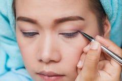 Femme asiatique de plan rapproché appliquant l'eye-liner sur l'oeil Image libre de droits