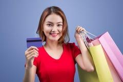 Femme asiatique de Santa tenant les paniers et la carte de crédit contre Photos libres de droits
