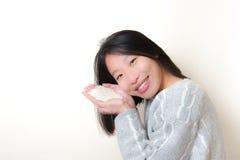 Femme asiatique de sourire avec du riz dans des mains Alimentez le concept du monde Image stock