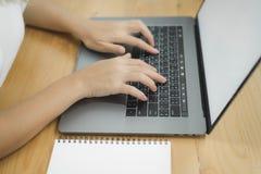 Femme asiatique de sourire de beaux jeunes travaillant sur l'ordinateur portable tandis qu'à la maison dans l'espace de travail d Images stock