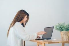 Femme asiatique de sourire de beaux jeunes travaillant sur l'ordinateur portable tandis qu'à la maison dans l'espace de travail d Image libre de droits