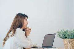 Femme asiatique de sourire de beaux jeunes travaillant sur l'ordinateur portable tandis qu'à la maison dans l'espace de travail d Photographie stock