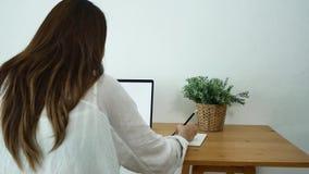 Femme asiatique de sourire de beaux jeunes travaillant sur l'ordinateur portable tout en se reposant dans un salon à la maison banque de vidéos