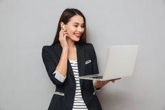 Femme asiatique de sourire d'affaires dans des écouteurs utilisant l'ordinateur portable photos libres de droits