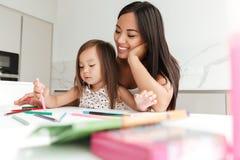 Femme asiatique de sourire enseignant sa petite fille à dessiner Photos libres de droits