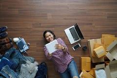 Femme asiatique de sourire de vue supérieure s'étendant sur le plancher en bois et écrivant dans le carnet Image libre de droits