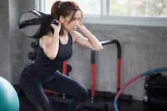 femme asiatique de sport dans la posture accroupie d'exercice de vêtements de sport avec avec le trainin images libres de droits
