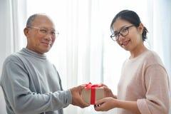Femme asiatique donnant un boîte-cadeau brun à l'homme plus âgé image libre de droits