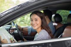 Femme asiatique employant le smartphone et la carte et hommes conduisant la voiture sur roa Image libre de droits