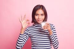 Femme asiatique en bonne santé buvant un verre de signe d'OK d'exposition de lait photos libres de droits