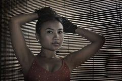 Femme asiatique en tissus de sport de gymnase regardant avec le fond de fenêtre d'abat-jour vénitiens Photographie stock