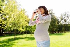 Femme asiatique enceinte heureuse avec l'appareil-photo au parc Photos stock