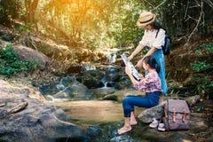 Femme asiatique et fille regardant une carte se reposant sur la roche près de la cascade à l'arrière-plan de forêt Images stock
