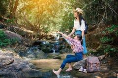 Femme asiatique et fille regardant une carte se reposant sur la roche près de la cascade à l'arrière-plan de forêt Photographie stock