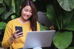 Femme asiatique excitée avec la promotion des ventes sur la boutique de site Web sur le lapto photos libres de droits