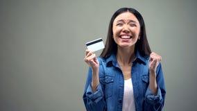 Femme asiatique extrêmement heureuse tenant la carte de crédit, bas taux d'intérêt pour créditer image libre de droits
