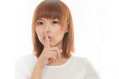 Femme asiatique faisant à une conservation le geste tranquille, d'isolement sur le blanc Image libre de droits