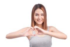 Femme asiatique faisant des gestes la forme de coeur avec des mains, d'isolement sur le blanc Photographie stock