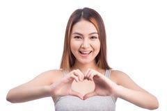 Femme asiatique faisant des gestes la forme de coeur avec des mains, d'isolement sur le blanc Image stock