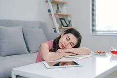 Femme asiatique fatiguée dormant près du divan après travail à la maison images libres de droits