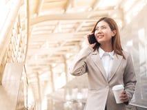 Femme asiatique futée d'affaires dans un costume avec le téléphone portable Photo stock