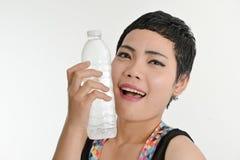 Femme asiatique futée tenant une bouteille de l'eau, concept sain photos stock