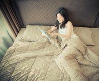 Femme asiatique heureuse à l'aide d'un comprimé sur le lit dans la chambre à coucher images libres de droits