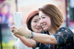 Femme asiatique heureuse avec l'ami prenant un selfie Photographie stock