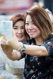 Femme asiatique heureuse avec l'ami prenant un selfie Image stock