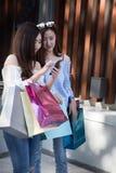 femme asiatique heureuse avec le smartphone et les paniers colorés à Photos libres de droits