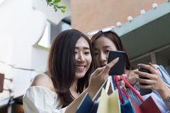 femme asiatique heureuse avec le smartphone et les paniers colorés à Image stock
