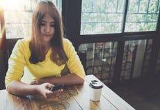 Femme asiatique heureuse causant à son téléphone portable tout en détendant en café pendant le temps gratuit, Image stock